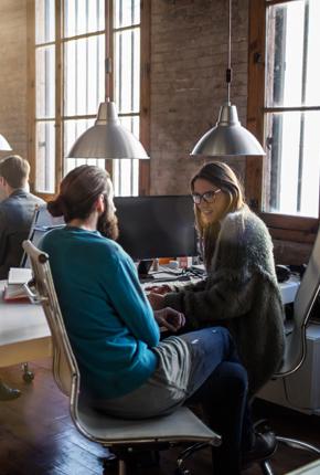 Menschen sitzen beim Schreibtisch