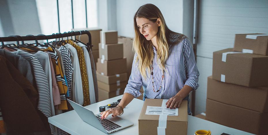Verbindung von On- und Offlinehandel anhand einer Dame mit Paket und Laptop