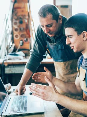 Zwei Männer am Laptop in der Arbeit