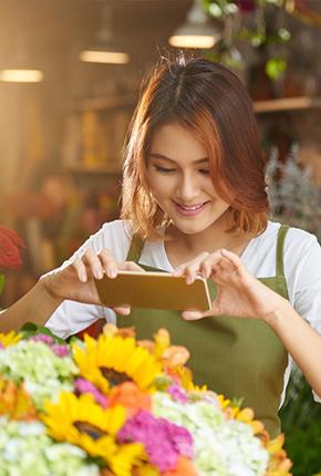 Frau mit Smartphone vor Blumenstrauß
