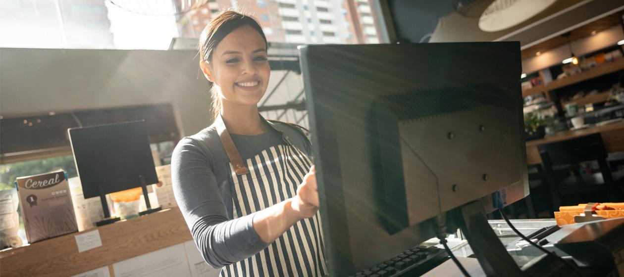 Frau mit Computer im stationären Einzelhandel