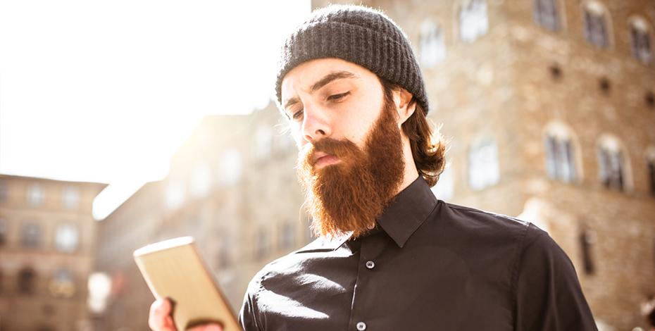 Mann mit Bart und Smartphone in Stadt