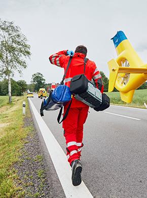 Sanitäter läuft aus dem Hubschrauber zu einem Verletzten
