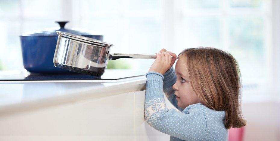 Kind in der Küche beim Spielen mit einem Topf