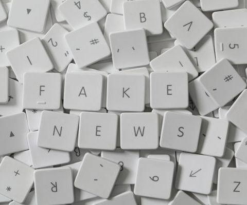 Text FAKE NEWS as keyboard letters lying on a sea of old